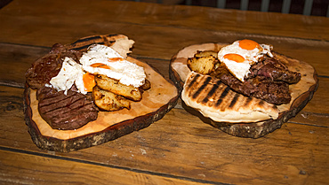 A gourmet meal of fresh meats and eggs, on a wood platter at the Blue Duck Lodge, a working cattle farm with a focus on conservation in Whanganui National Park; Retaruke, Manawatu-Wanganui, New Zealand