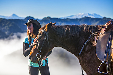 The Blue Duck lodge located in the Whanganui National Park is a working cattle farm with a focus on conservation. Travellers go to a scenic viewpoint to watch the sunrise over the rainforest. A Cowgirl stands with her horse; Retaruke, Manawatu-Wanganui, New Zealand