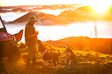 The Blue Duck lodge located in the Whanganui National Park is a working cattle farm with a focus on conservation. Travellers go to a scenic viewpoint to watch the sunrise over the rainforest. A man stands drinking coffee with dogs at his feet; Retaruke, Manawatu-Wanganui, New Zealand
