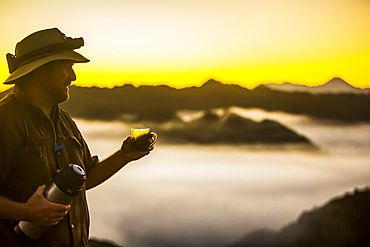 The Blue Duck lodge located in the Whanganui National Park is a working cattle farm with a focus on conservation. Travellers go to a scenic viewpoint to watch the sunrise over the rainforest. A man stands drinking coffee and holding a thermos; Retaruke, Manawatu-Wanganui, New Zealand