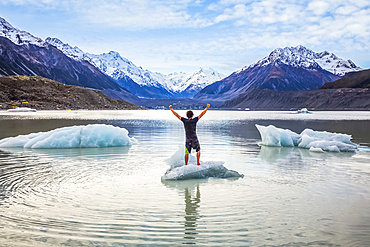 Man standing on small ice berg in the middle of a glacial lake in Mount Cook National Park; Canterbury, New Zealand