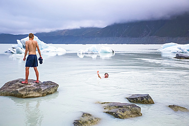 Men swimming in the icy glacial lakes of Mount Cook National Park; Canterbury, New Zealand