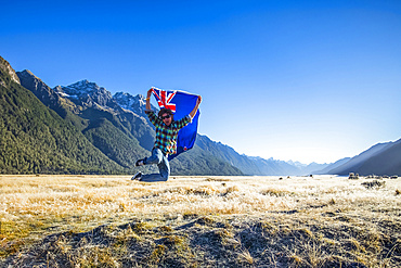 A man jumps in the air with the New Zealand flag in Fiordland National Park; Southland, New Zealand