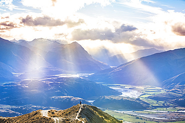 Man standing on mountaintop at Roys Peak with beautiful rays of sunlight after the strenuous hike to the lookout to see the spectacular views of the lakes and surrounding mountains of the Southern Alps near Wanaka; Otago, New Zealand