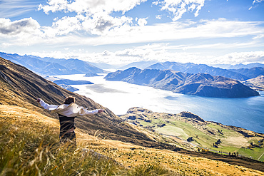The strenuous yet highly rewarding hike to Roys Peak in Wanaka. The hike is difficult but the views are spectacular. A traveler celebrates at the summit; Wanaka, Otago, New Zealand