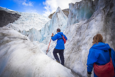Travelers exploring the famous Franz Josef Glacier with its, blue ice caves, deep crevasses and tunnels that mark the ever changing ice formations; West Coast, New Zealand
