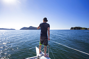 View taken from behind of a man standing at the bow of a catamaran on a boat tour in the Abel Tasman National Park; Tasman, New Zealand