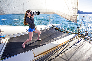 Woman standing on a catamaran taking photographs with a camera with a telephoto lens on a boat tour through the Abel Tasman National Park; Tasman, South Island, New Zealand