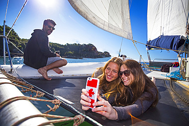 Friends taking a selfie onboard a catamaran boat tour through Abel Tasman National Park with a man smiling in the background; Tasman, New Zealand