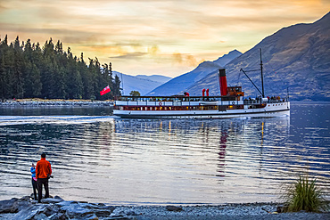 Tourists watching the famous TSS Earnslaw takes a sunset tour around Queenstown's Lake Wakatipu; Otago, New Zealand