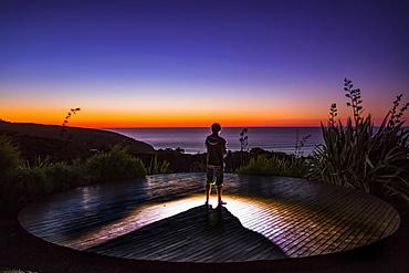 A man watches the sunset from the cliffs of Raglan, New Zealand; Raglan, Waikato, New Zealand