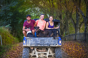 Three young adults sit in the back of a dune buggy with dogs after a muddy tour; Retaruke, Manawatu-Wanganui, New Zealand