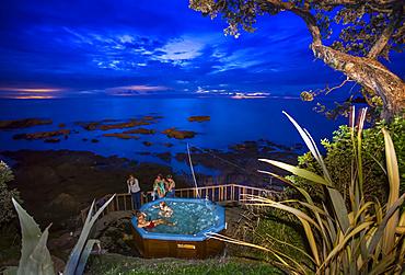 Travellers enjoy a spa pool located on the Eastern Cape shoreline of New Zealand; Te Kaha, Bay Of Plenty, New Zealand