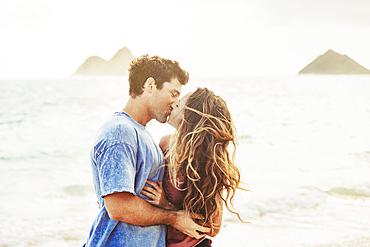 Millennial couple kissing on Lanikai Beach with the Mokes Islands in the background; Lanikai, Oahu, Hawaii, USA