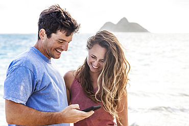 A young Millennial couple looking at a smart phone on Lanakai Beach with the Mokes Islands in the background; Lanakai, Oahu, Hawaii, USA