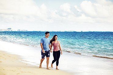 A Millennial couple walking along Lanikai Beach with Mokapu Point and the Moku Manu Islands in the background; Lanikai, Oahu, Hawaii, USA