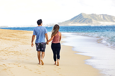 A view from behind of a Millennial couple walking along Lanikai Beach with Mokapu Point in the background; Lanikai, Oahu, Hawaii, USA