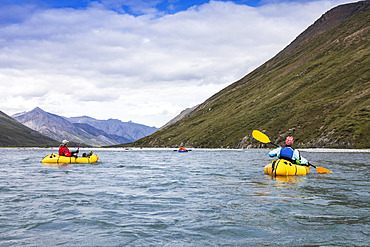 One woman paddling, one floating their yellow packraft boats downriver towards man in blue boat in background on a sunny, summer day on the Marsh Fork river;  Brooks Range, Arctic National Wildlife Refuge (NWR), Alaska, USA