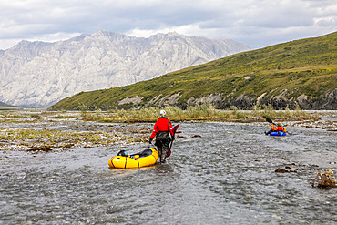 Caucasian woman wearing red drysuit, drags her yellow packraft down a shallow braid of the Marsh Fork river, while a caucasian man wearing orange drysuit paddles a blue boat downriver, through the Brooks Range mountains, Arctic National Wildlife Refuge, Alaska on a sunny summer day; Alaska, United States of America
