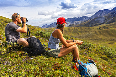 Caucasian man in his 30's, sitting down and looking through binoculars, glassing for wildlife, while  a caucasian woman sitting down next to in her 40's look at the mountains in the same direction, while on a break from  hiking, Brooks Range; Alaska, United States of America