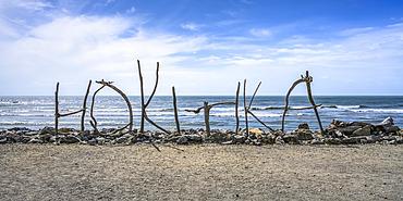 Sign made out of driftwood standing on Hokitika Beach; Hokitika, West Coast Region, South Island, New Zealand