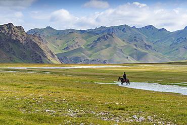 Horseman riding in Kurumduk valley, Naryn province, Kyrgyzstan, Central Asia, Asia