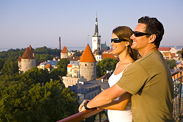 A couple take in the views of lower Old Town with Oleviste Church in the background, Tallinn, Estonia, Europe