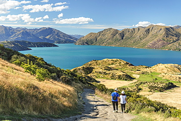 Hiker on Roy's Peak Track enjoying the view over Lake Wanaka, Mount-Aspiring National Park, Otago, South Island, New Zealand, Pacific