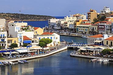 Voulismeni Lake, lined with cafes and restaurants, bridge crosses a narrow channel, Agios Nikolaos, Lasithi, Crete, Greek Islands, Greece, Europe