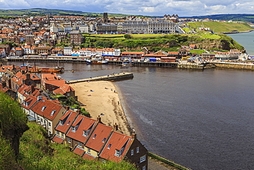 Tate Hill Beach, red roofed houses, town on West Cliff with backdrop of green hills in summer, Whitby, North Yorkshire, England, United Kingdom, Europe