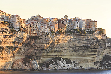 Old citadel townhouses and church at dawn, in early morning light, seen from the sea, Bonifacio, Corsica, France, Mediterranean, Europe