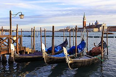 Gondolas, San Marco waterfront at sunset in winter, view to San Giorgio Maggiore, Venice, UNESCO World Heritage Site, Veneto, Italy, Europe