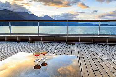 Glowing cognac (brandy) reflections, glass table at sunset, cruise ship stern, Resurrection Bay, Kenai Peninsula, Alaska, United States of America, North America