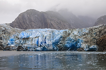 Blue ice face and floating ice, Sawyer Glacier and mountains, misty conditions, Stikine Icefield, Tracy Arm Fjord, Alaska, United States of America, North America