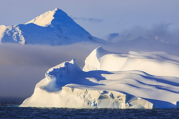 Huge non-tabular iceberg, mountains, evening light and mist, Bransfield Strait, South Shetland Islands, Antarctica, Polar Regions