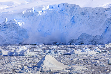 Ice avalanche, glacial calving into iceberg filled Neko Harbour, early morning sun, Graham Land, Antarctic Continent, Antarctica, Polar Regions
