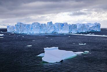 Large blue tabular iceberg, small iceberg and coast of Errera Channel, Danco Coast, Antarctic Peninsula, Antarctica, Polar Regions