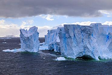 Large blue tabular iceberg and coast of Errera Channel, Danco Coast, Antarctic Peninsula, Antarctica, Polar Regions