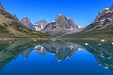 Reflections, beautiful mountains, rugged South Skjoldungen Fjord and Island, glorious weather, remote South East Greenland, Denmark, Polar Regions