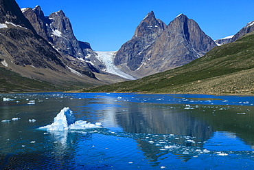 Blue iceberg, pyramidal peaks, glacier, rugged South Skjoldungen Fjord and Island, glorious weather, remote East Greenland, Denmark, Polar Regions