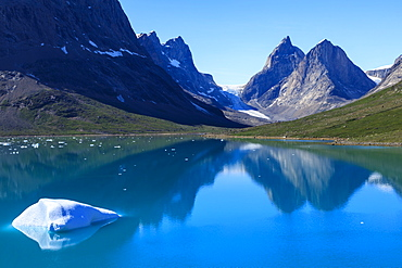 Iceberg, pyramidal peaks, reflections, blue green waters, South Skjoldungen Fjord, glorious weather, remote South East Greenland, Denmark, Polar Regions