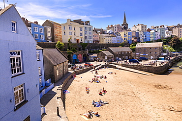 Colourful historic town, St. Mary's church, from Harbour Beach, sunbathers on a sunny day, Tenby, Pembrokeshire, Wales, United Kingdom, Europe