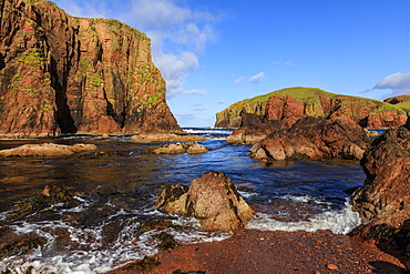 North Ham Bay, deep inlet, lichen covered red granite cliffs and stacks, seaweed, Muckle Roe Island, Shetland Isles, Scotland, United Kingdom, Europe