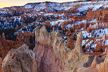 Hoodoos, rim and snow lit by dawn light in winter, Queen's Garden Trail at Sunrise Point, Bryce Canyon National Park, Utah, United States of America, North America