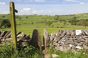 Footpath sign and stone stile with dry stone wall, near Alstonefield, Peak District National Park, Staffordshire, England, United Kingdom, Europe