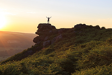 On top of the world, visitor enjoys sunset on Curbar Edge with arms aloft, Peak District National Park, Derbyshire, England, United Kingdom, Europe