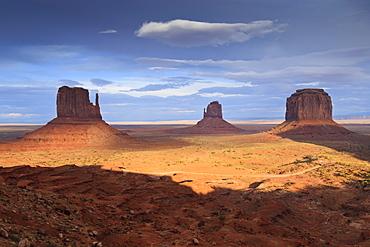 Mittens at dusk, late evening sun lights the desert floor, Monument Valley Navajo Tribal Park, Utah Arizona border, United States of America, North America