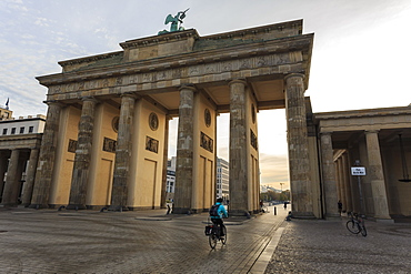Cyclist approaches the Brandenburg Gate in the early morning, Historic Mitte, Berlin, Germany, Europe