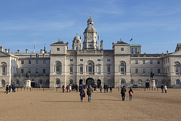 Tourists walk towards the arch of Horse Guards Parade under a winter's blue sky,  Whitehall, London, England, United Kingdom, Europe
