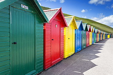 Row of colourful beach huts and their shadows with green hill backdrop, West Cliff Beach, Whitby, North Yorkshire, England, United Kingdom, Europe